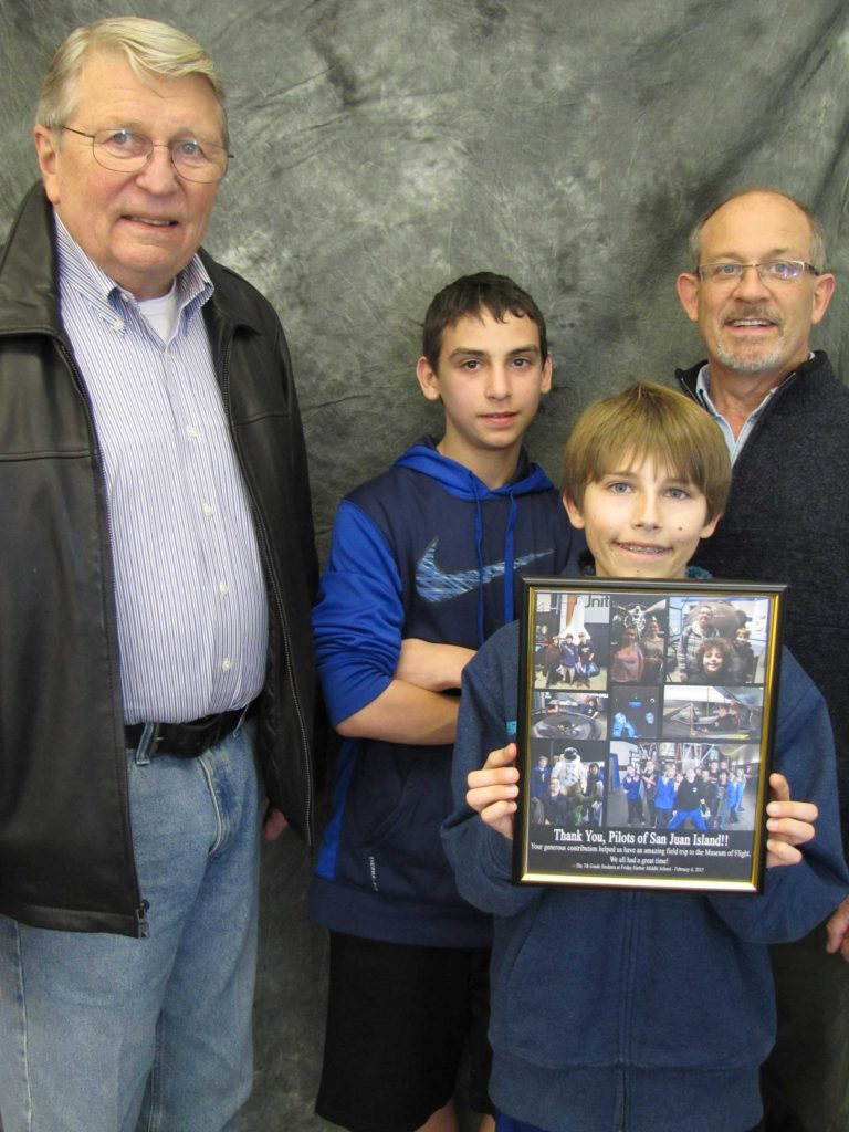 "the presentation of a ""Thank You collage"" from the 7th grade to the San Juan Pilots Association and the San Juan Public Schools Foundation.   Left to right:  Bob Tauscher, San Juan Pilots Association; Gavin Flaum, student; Levi Doenges, student; Mike Taylor, San Juan Public Schools Foundation.  (Gavin and Levi currently engage in ""ground school"" private pilot training and hope to earn pilot licenses eventually.)"